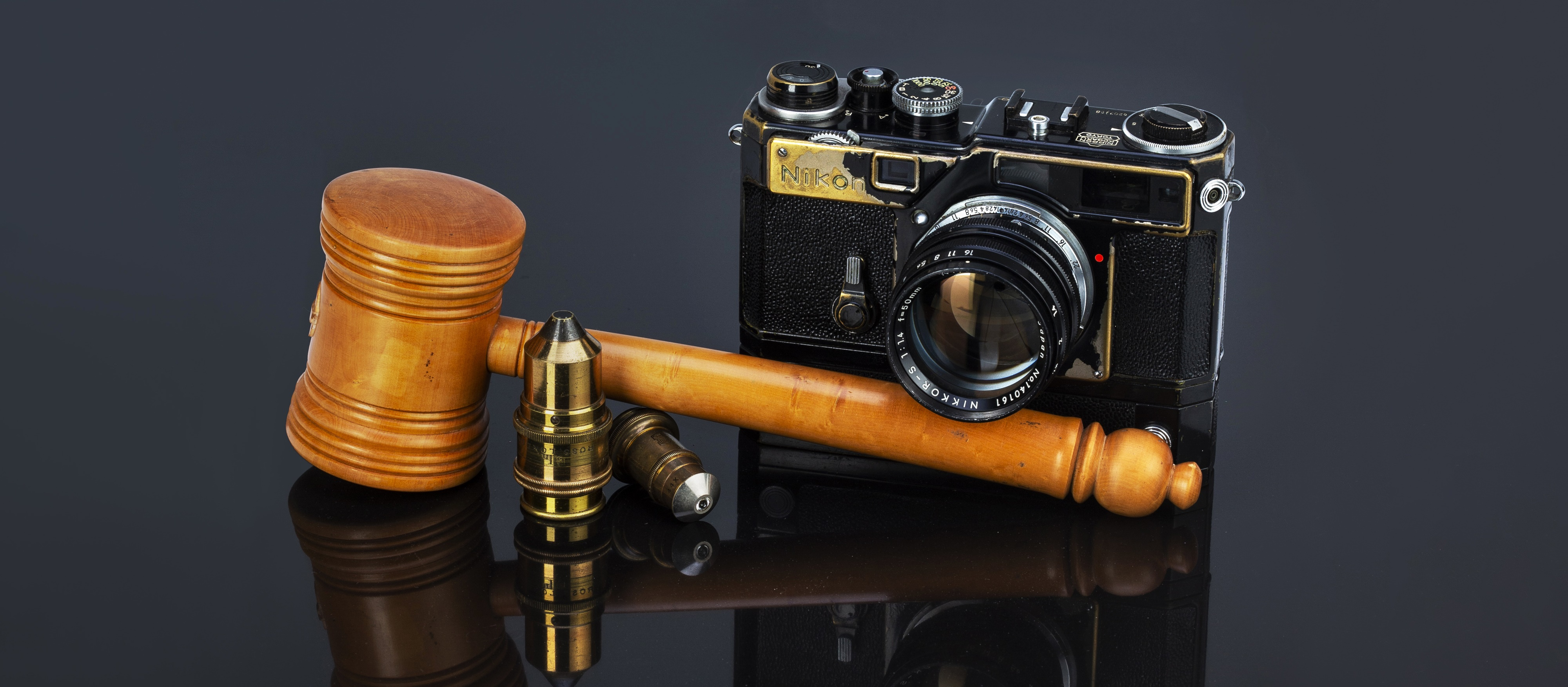 A auctioneers gavel and a Nikon SP Rangefinder Camera with black paint sit on black reflective material, with two brass microscope objective lenses forming part of the arangement