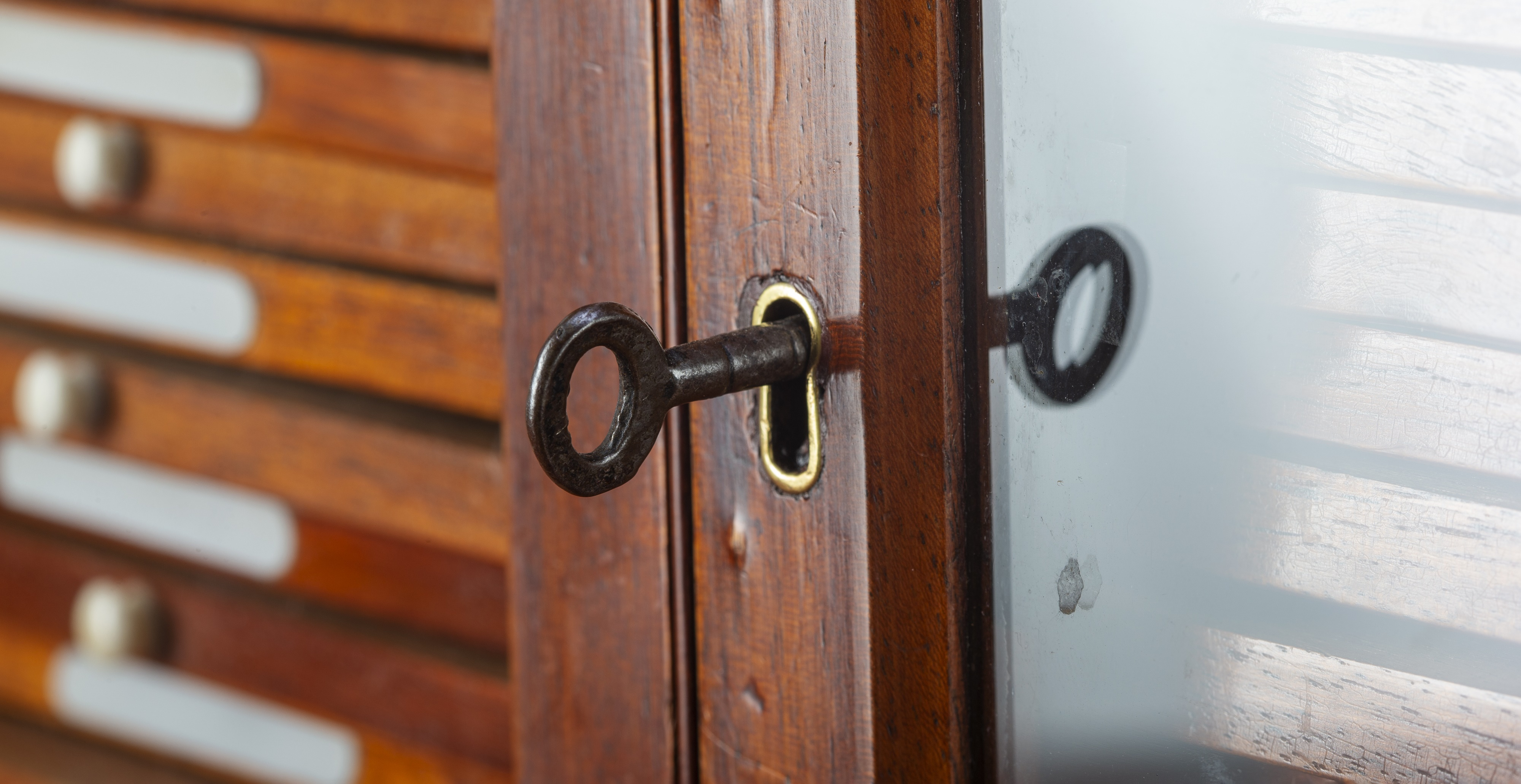 A lock with a key inserted in the door of a victorian style microscope cabinet to symbolically represent the mutual trust set out in the terms in conditions that follow