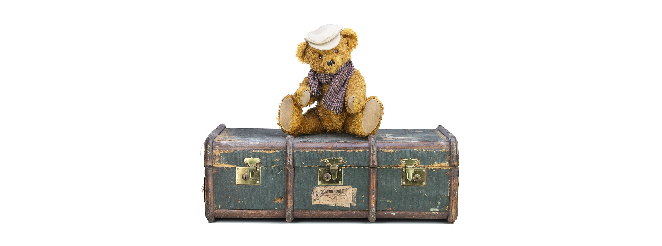 A studio photograph of a teddy bear sitting on an old luggage trunk on a white background