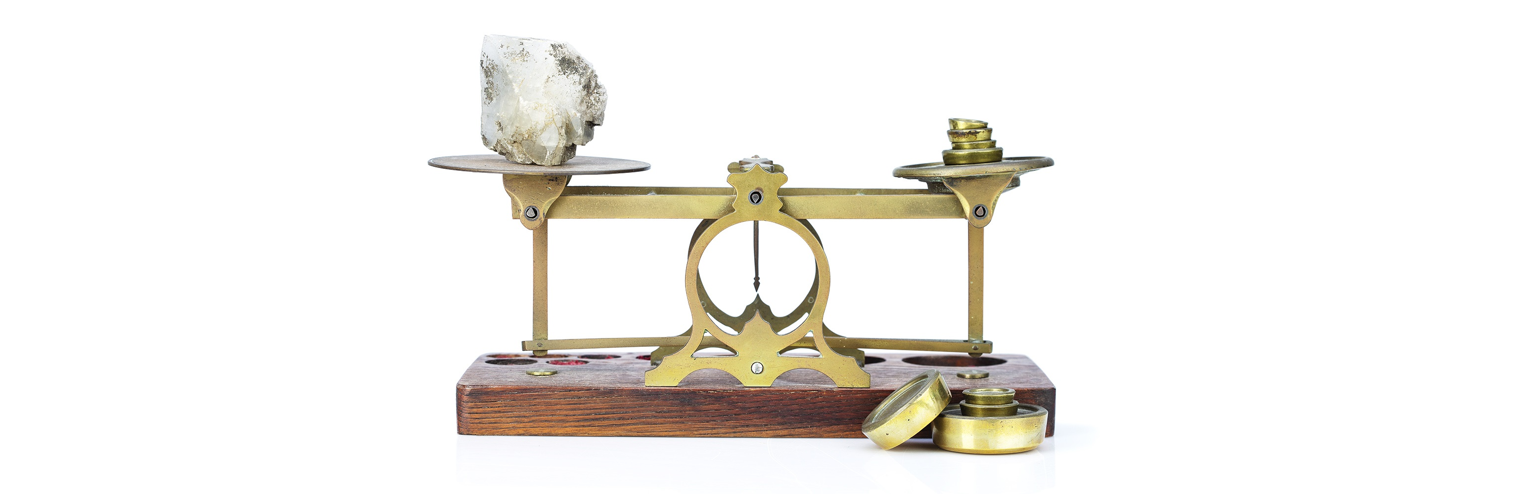 A set of scales with a piece of rock or crystal and brass weoghts on the other side. Both sides are in a state of balance